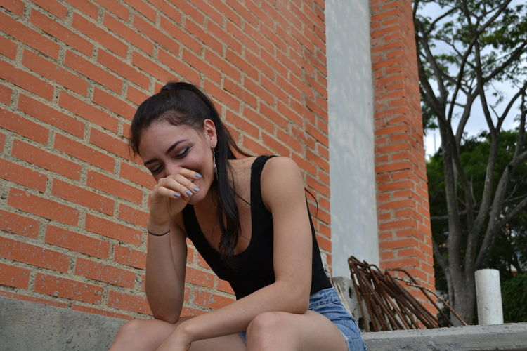 Young woman sitting against brick wall