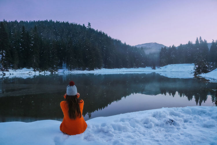 Rear view of woman sitting by lake during winter