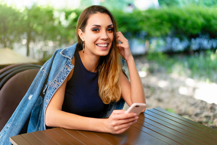 Portrait of smiling woman using mobile phone at table
