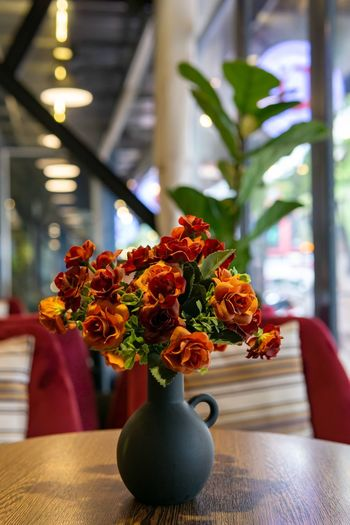 Coffee shop decoration. Coffee Shop Arrangement Bouquet Cafe Close-up Decoration Flower Flower Arrangement Flower Head Flower Pot Flowering Plant Focus On Foreground Freshness Houseplant Indoors  No People Orange Flower Plastic Flower Red Flower Table Vase