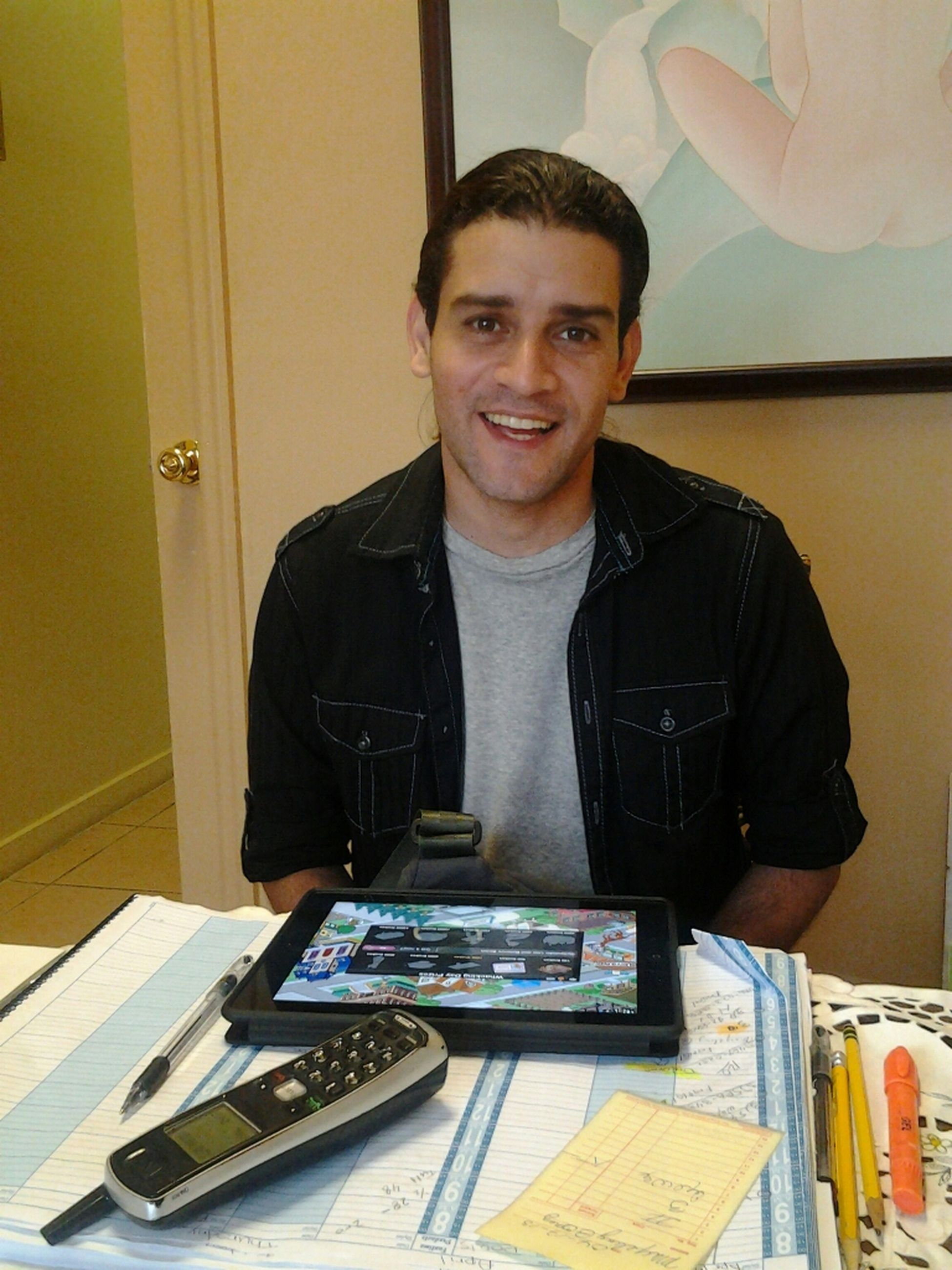 indoors, casual clothing, lifestyles, young adult, person, front view, looking at camera, young men, portrait, leisure activity, sitting, standing, holding, three quarter length, technology, waist up, table, smiling