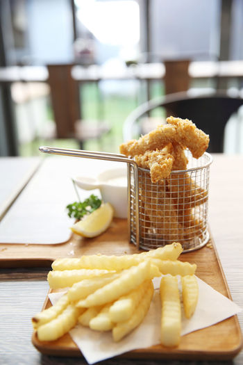 Fish And Chips Food And Drink Food Freshness Table Indoors  Ready-to-eat Potato Prepared Potato Focus On Foreground Healthy Eating French Fries Still Life Wellbeing No People Fried Fast Food Selective Focus Wood - Material Deep Fried  Snack Tray
