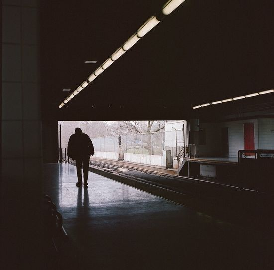 Rear view of silhouette man walking on illuminated railroad station