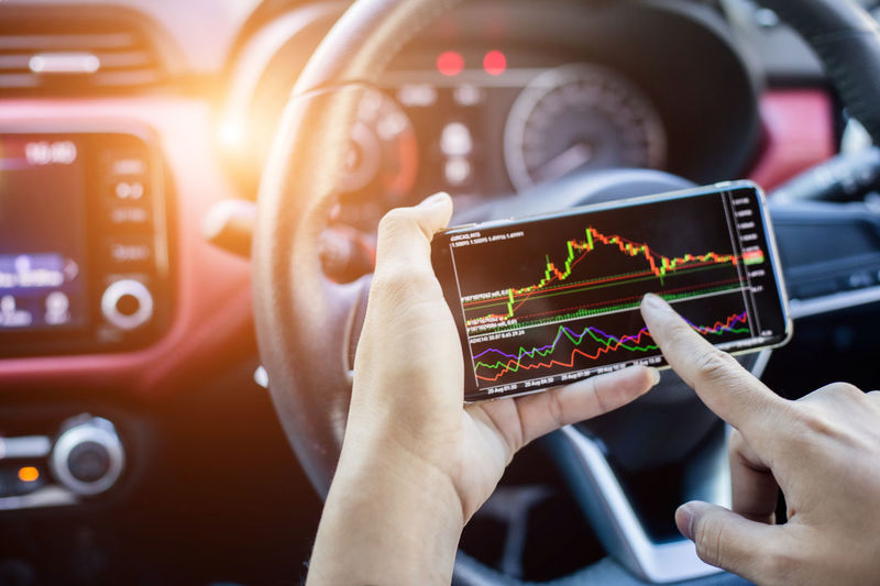 Midsection of man using mobile phone in car