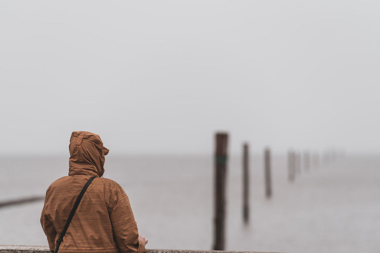 Rear view of person standing by sea