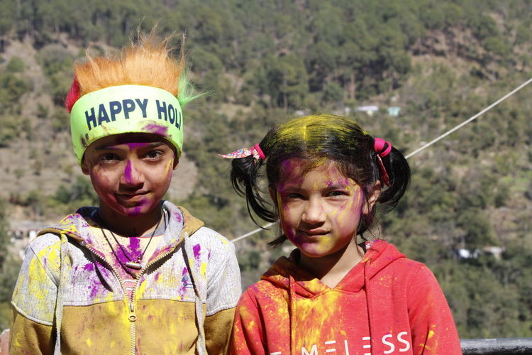Portrait of siblings with face paint outdoors