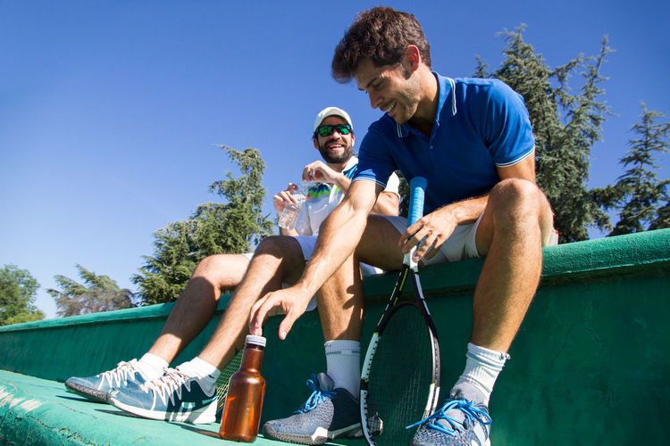 Two professional players hydrating and resting after a hard game of tennis in a sunny day. Court Drinking Water Hydration Lifestyle Set Tennis Thirst Adults Bottle Caucasian Drinking Game Hydrate  Leisure Activity Match Men Outdoors Pause People Players Rest Resting Sport Water Young Adult