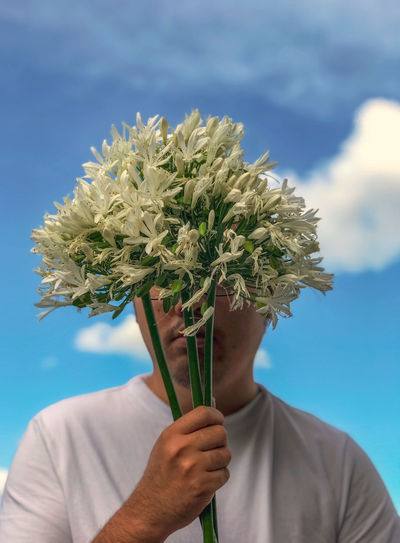 Midsection of man holding bouquet of white flowers against cloudy sky
