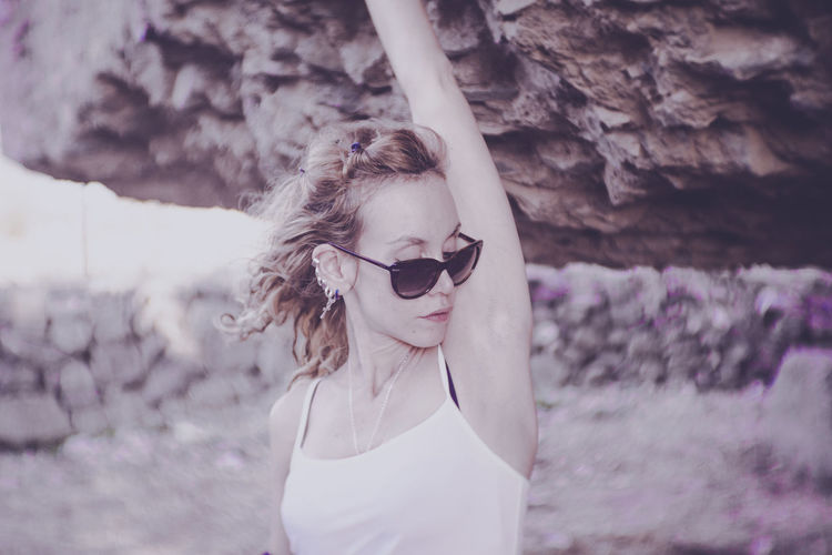 Woman Wearing Sunglasses Under Rock