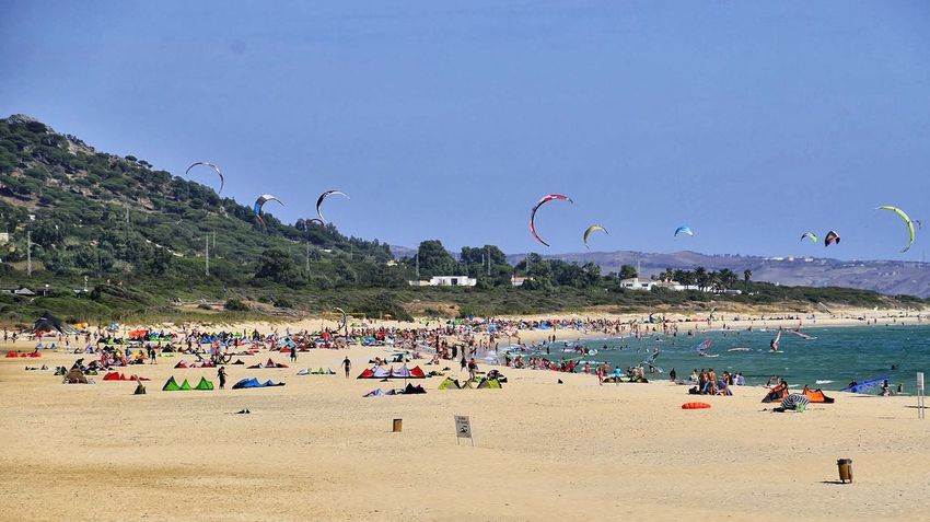 Beach Sand Large Group Of People Summer Water Fun Leisure Activity Vacations Nature Sea Enjoyment Outdoors Flying Day Sky Beauty In Nature Weekend Activities Amusement Park People Lifestyles Tarifa Spain Sand Dune Kitesurfing