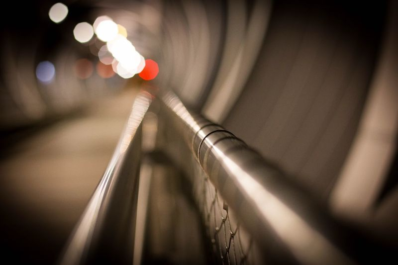 Close-up of railing in illuminated tunnel