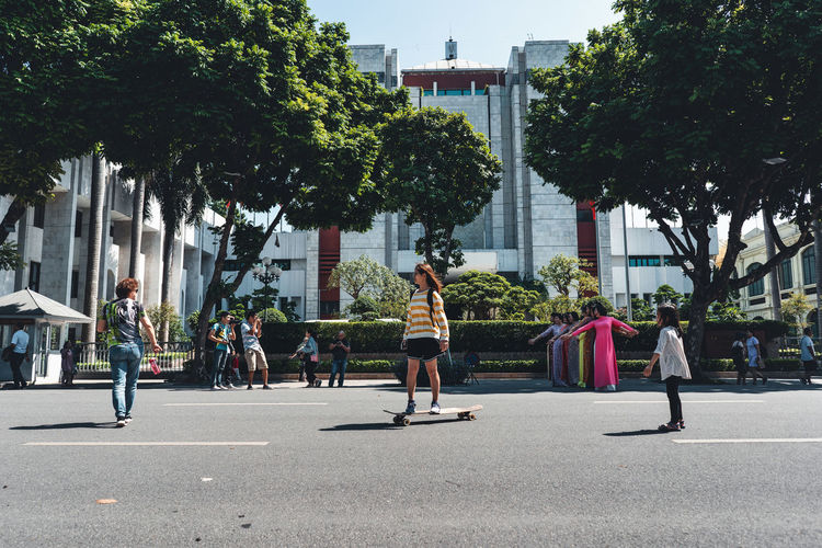 People on street against trees in city