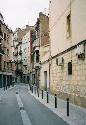 Residential buildings by street against clear sky