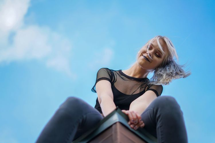 Low angle view of woman sitting against blue sky