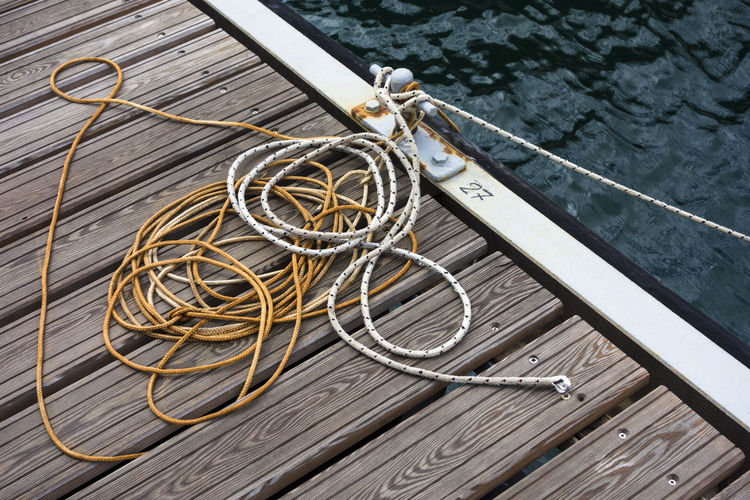 Tangled rope tied on cleat at pier