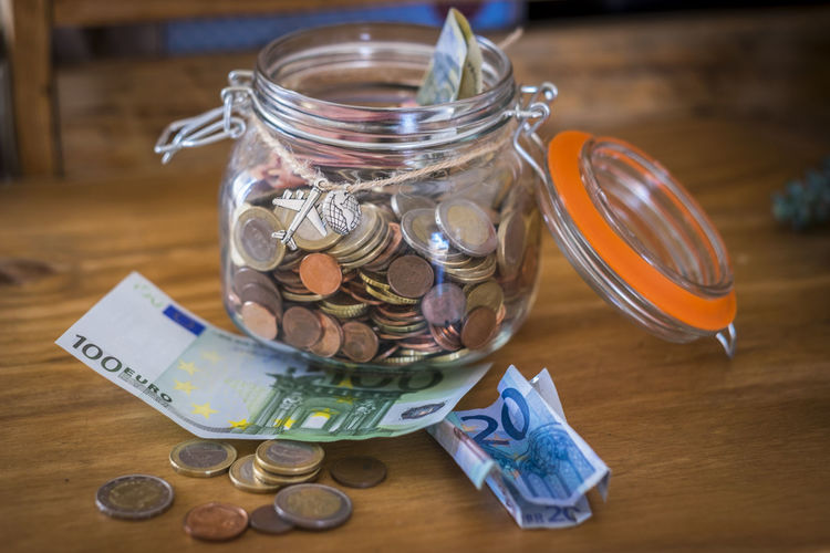glass vase full of money cash and coins ready to be used to travel or realize dreams for people - modern society business concept Jar Table Container Finance Business Currency Indoors  Coin Wealth Paper Currency Still Life Savings No People Close-up Glass - Material Food And Drink Food Transparent Large Group Of Objects Wood - Material Economy Crockery Money Euro Dreaming Vacations Expensive Business Concept People Bank Brexit Consumerism Currency Honesty