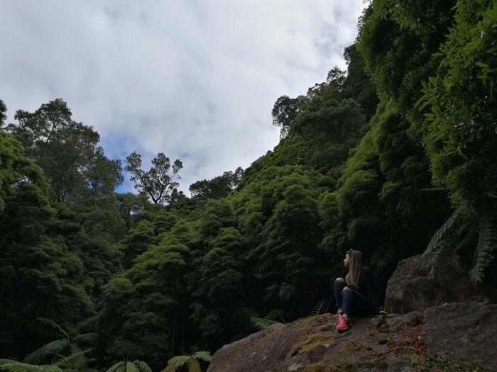 Young Woman Sitting On Rock Against Trees In Forest