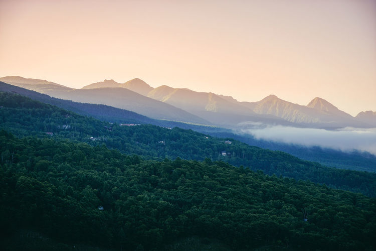 Scenic view of tree mountains against clear sky during sunset