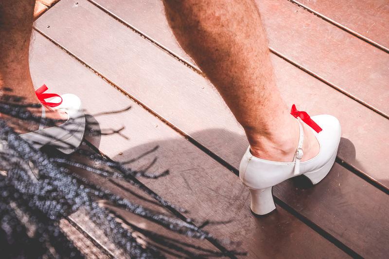 Low section of man wearing high heels standing on hardwood floor