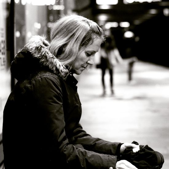 Side View Of Woman Wearing Warm Clothing While Sitting Outdoors