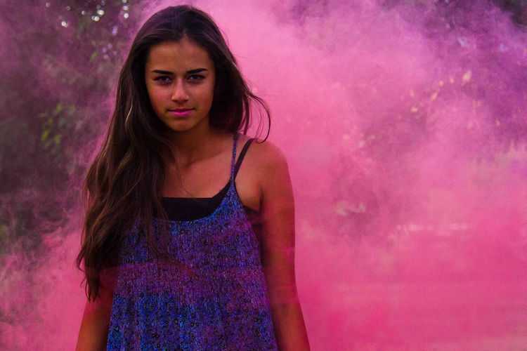 Portrait Of Confident Woman Standing Amidst Pink Smoke