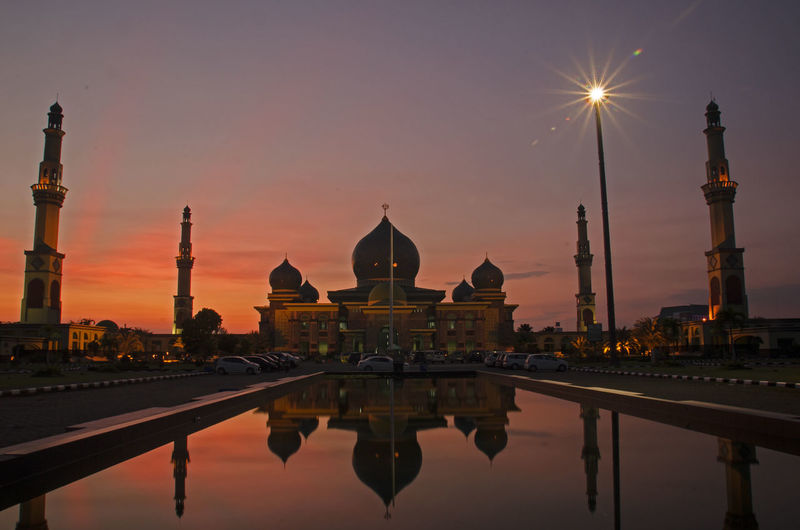 Facade of an nur great mosque against sky during sunset