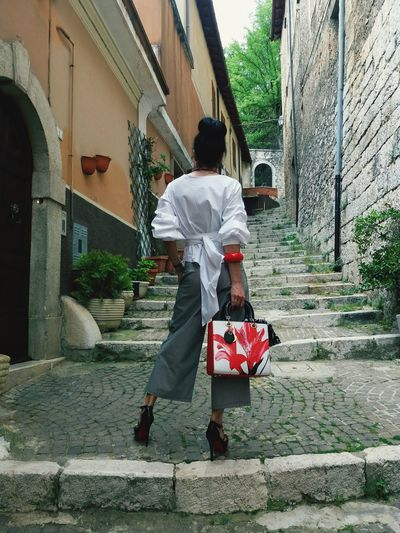 Rear view of mature woman standing on steps