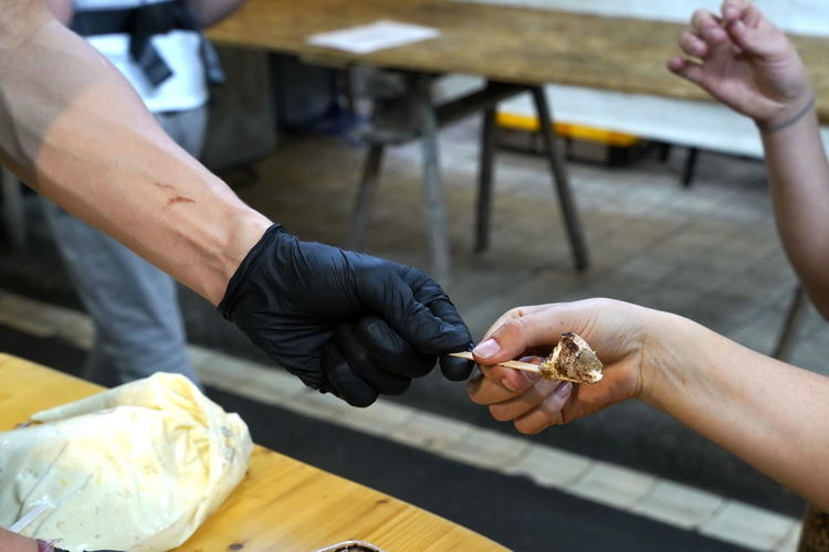 Cropped hand giving food to customer for tasting
