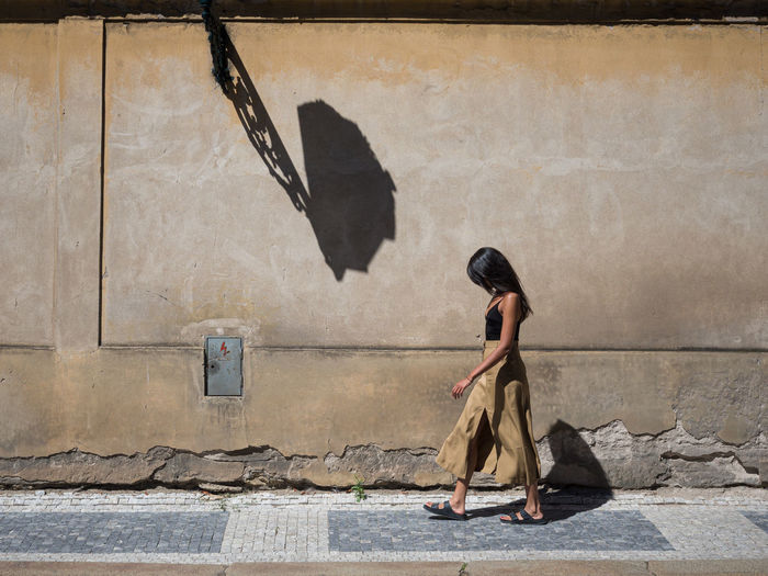 Side view of woman walking on sidewalk against wall