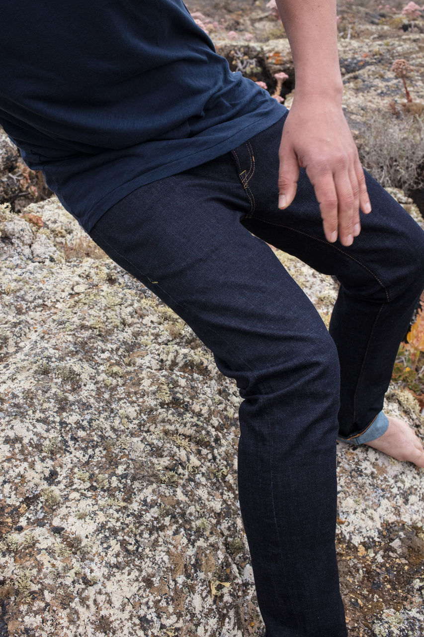 low section, one person, human leg, real people, human body part, leisure activity, day, lifestyles, casual clothing, body part, nature, outdoors, midsection, hand, land, human hand, men, standing, rock, jeans, human foot, human limb