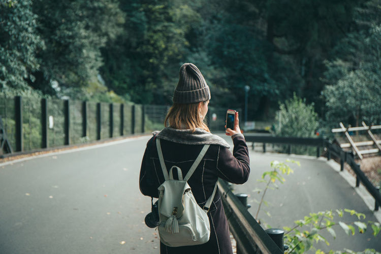 Rear view of woman photographing on mobile phone standing on road