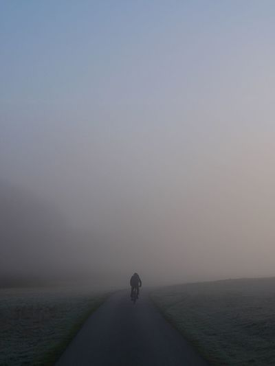 Rear View Of Man Riding Bicycle On Road During Foggy Weather