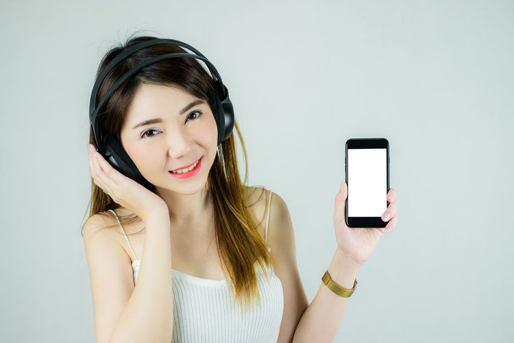 Portrait of young woman using smart phone against white background