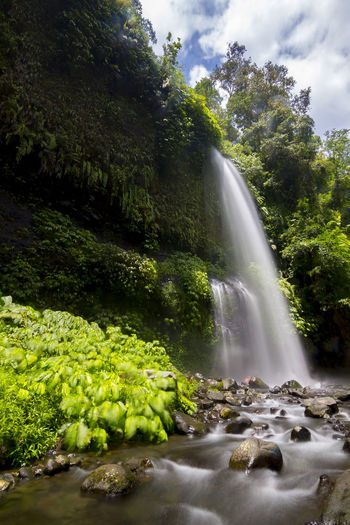 Scenic view of waterfall against sky