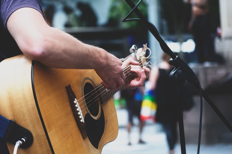 Cropped Image Of Man Performing With Acoustic Guitar On Street