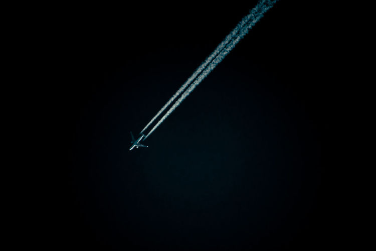 Airplane Air Vehicle Airplane Black Background Cloud - Sky Copy Space Flying Mid-air Mode Of Transportation Motion Night No People on the move Plane Sky Speed Transportation Vapor Trail
