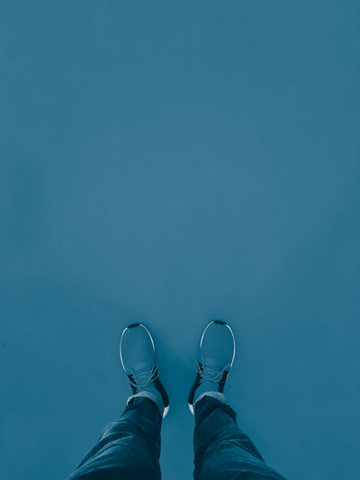 Low section of man standing on blue background