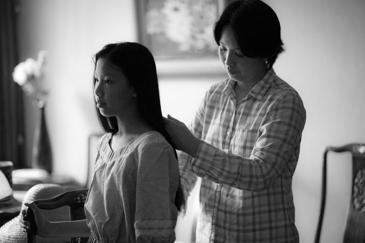 Woman combing daughter's hair