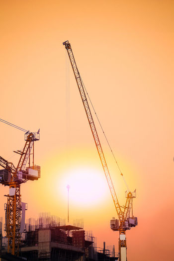 Cranes Against Sky During Sunset