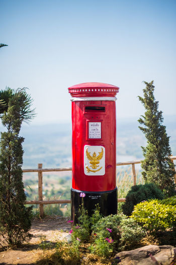 Red telephone booth by trees against sky