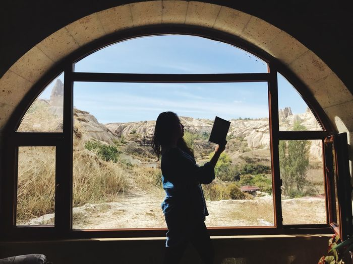 Side view of woman reading book by window at home