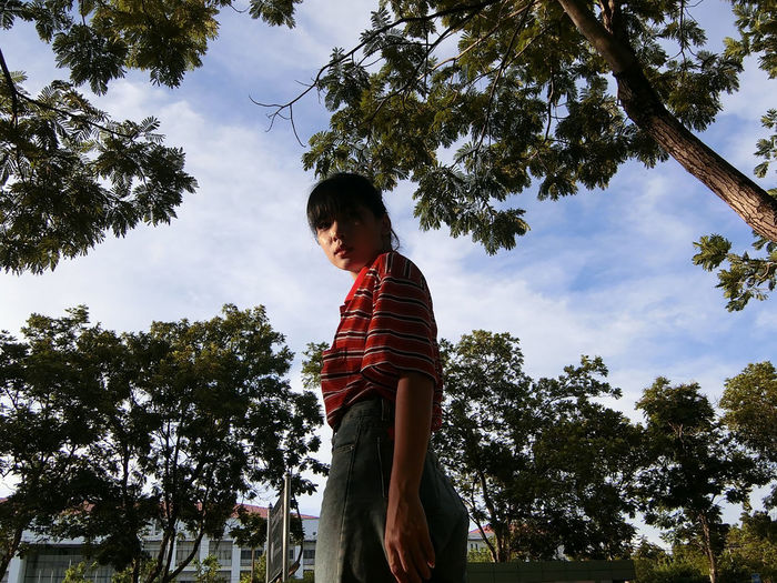 Low angle view of boy standing by trees against sky