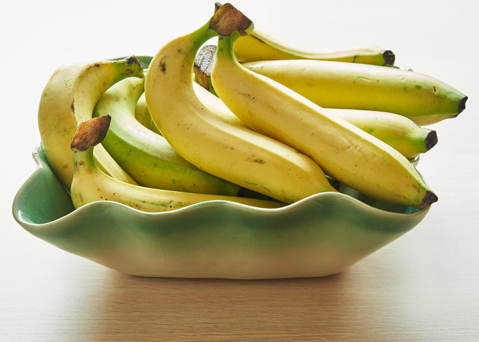 Bunches of delicious bananas in the bowl on the table Bananas Yellow Background Fruit Ripe Food Bunch Organic Healthy Sweet Tropical Natural Fresh Nutrition Diet Raw Color Health Closeup Vegetarian Appetizing  White Nature Tasty Object Group Table Freshness Delicious Ingredient Vitamin Breakfast Refreshment Vegetables Light Bowl