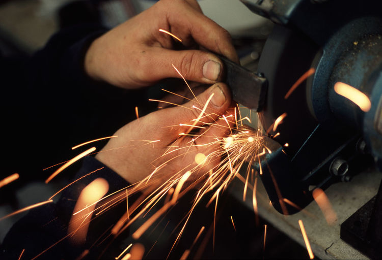 factory worker grinding burrs off a metal bar Abrasive BURR Close-up Cropped Deburr Factory Fingers Flying Grind Grinding Hands Holding Light Manufacturing Metal Metallic Part Of Person Sharp Sharpshutters Spark Sparkle Sparks Unrecognizable Person Wheel