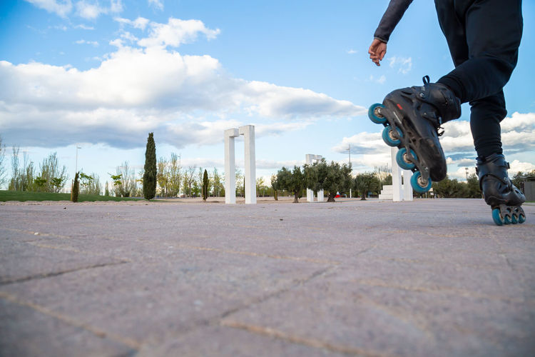 Low section of man skateboarding on city against sky