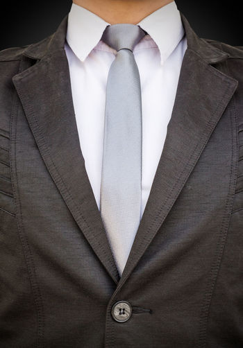 Midsection of businessman standing against black background