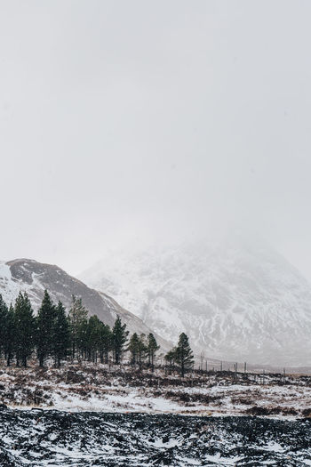 Scenic view of snow covered landscape and mountains against clear sky