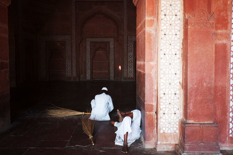Male cleaners with brooms at mosque