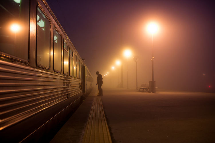 Silhouette Man Standing By Train At Railroad Station During Night