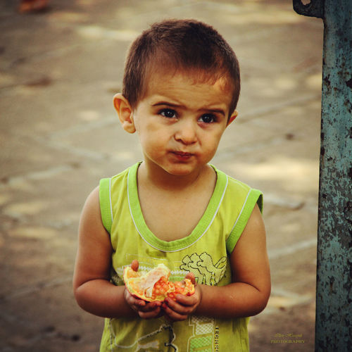Cute boy holding fruit while standing on footpath
